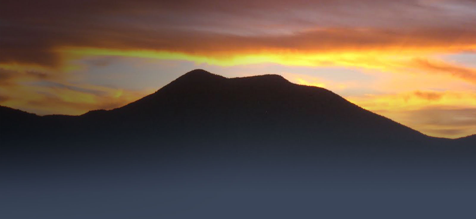 Mountain silhouette against yellow and orange susnet